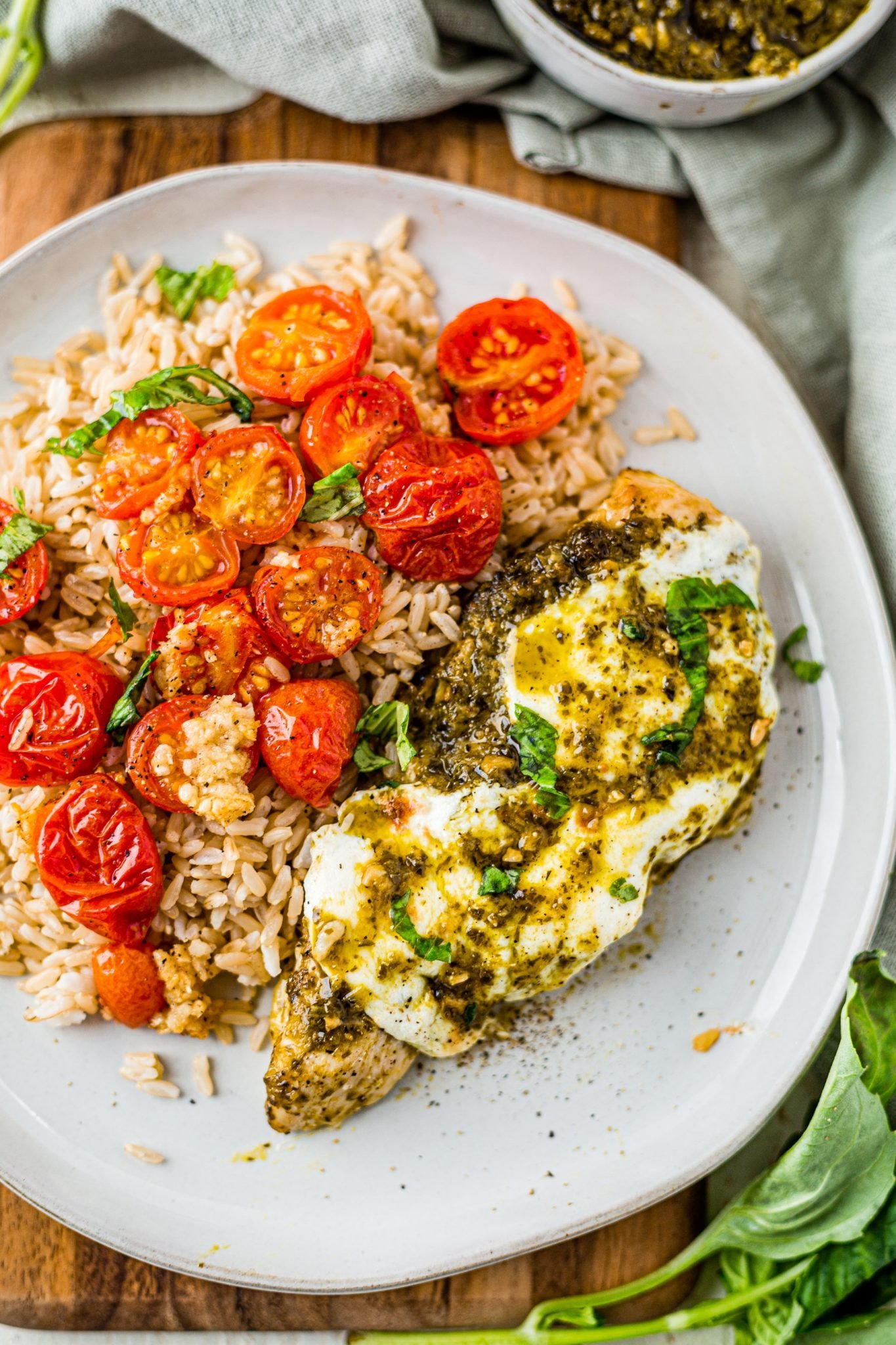 pesto chicken on a white plate topped with mozzarella cheese and served with rice and roasted tomatoes
