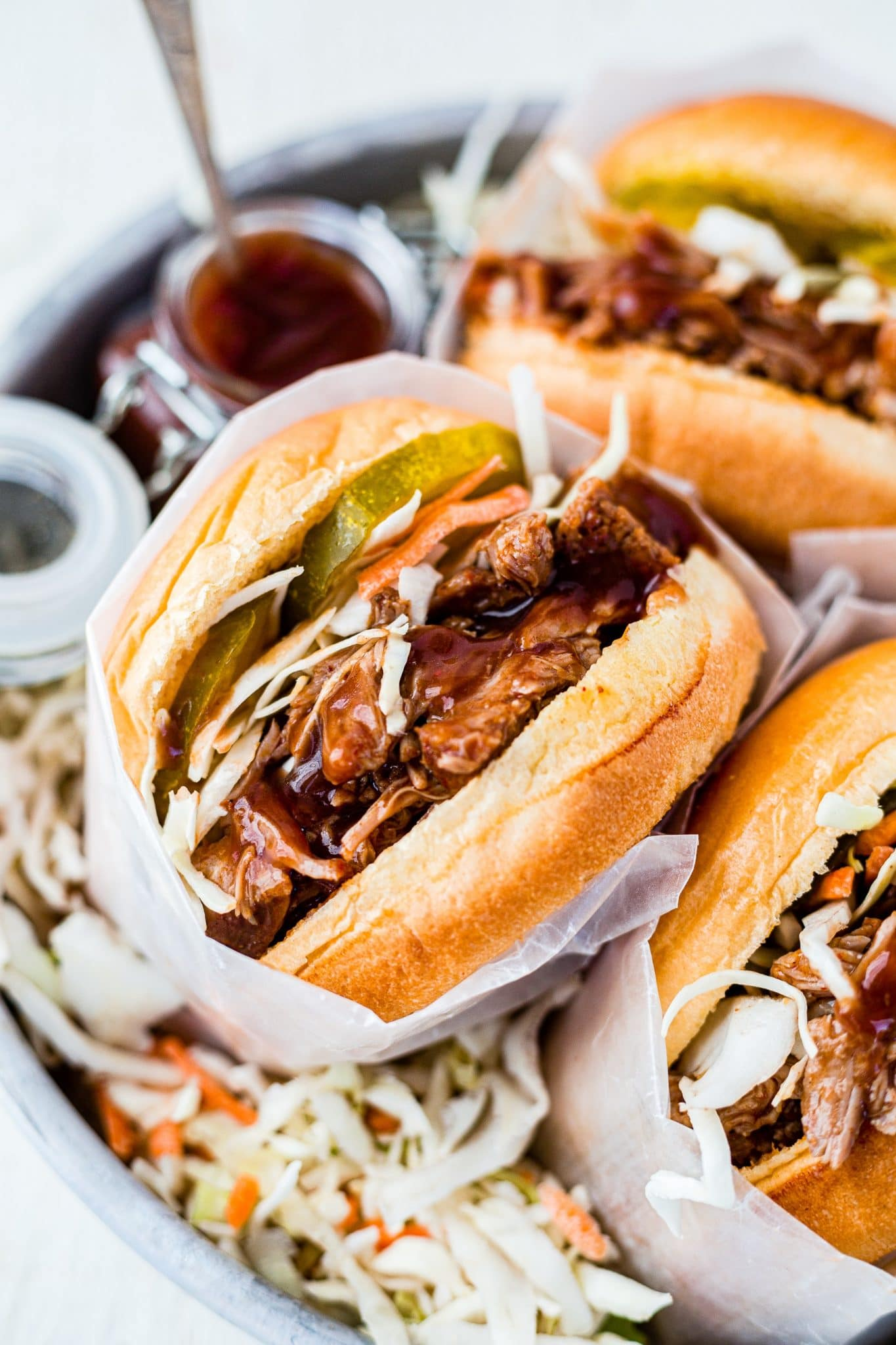 instant pot pulled pork sandwich topped with coleslaw and pickles and wrapped in parchment paper to serve