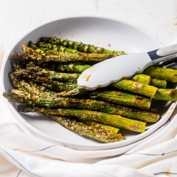 a pound of air fryer asparagus in a white serving dish with tongs for serving