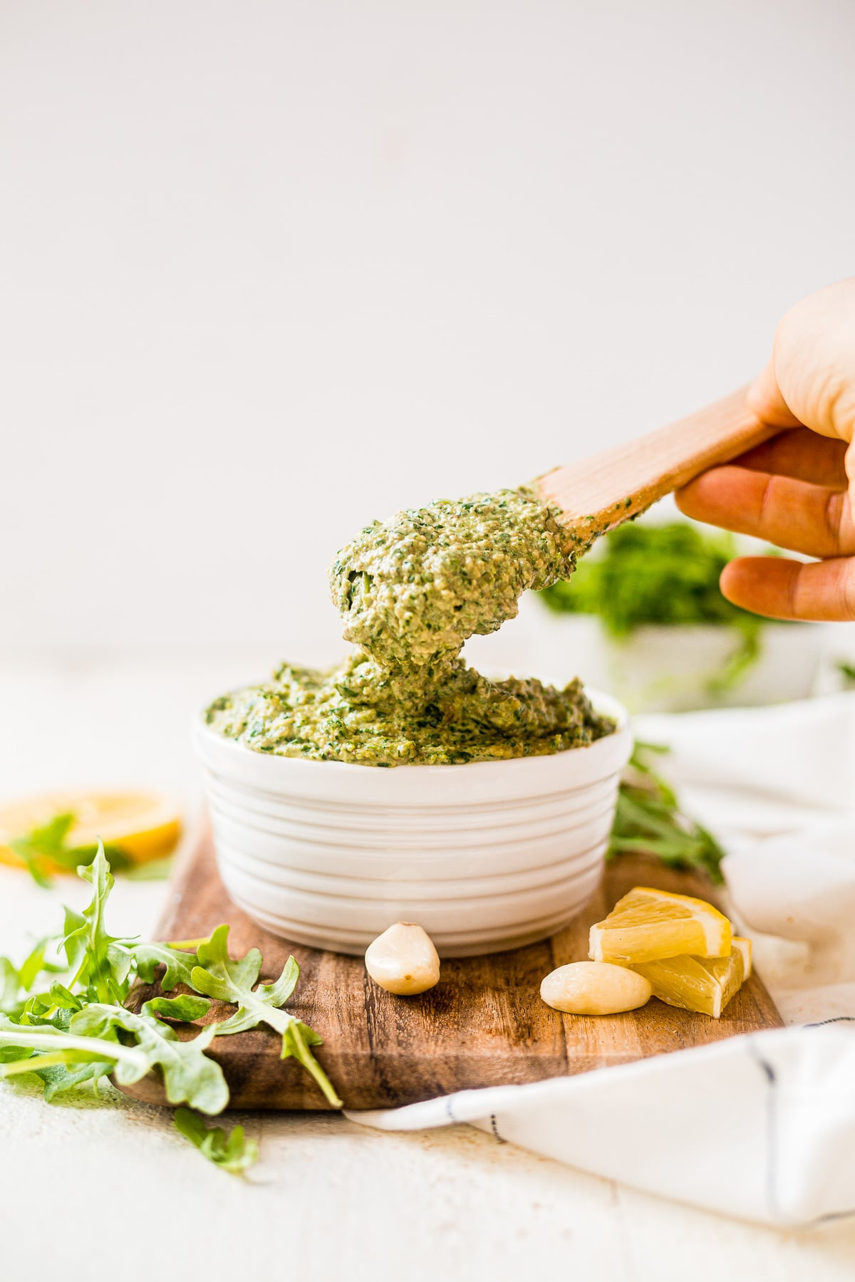 wooden spoon scooping out a heaping tablespoon of arugula pesto from a white bowl