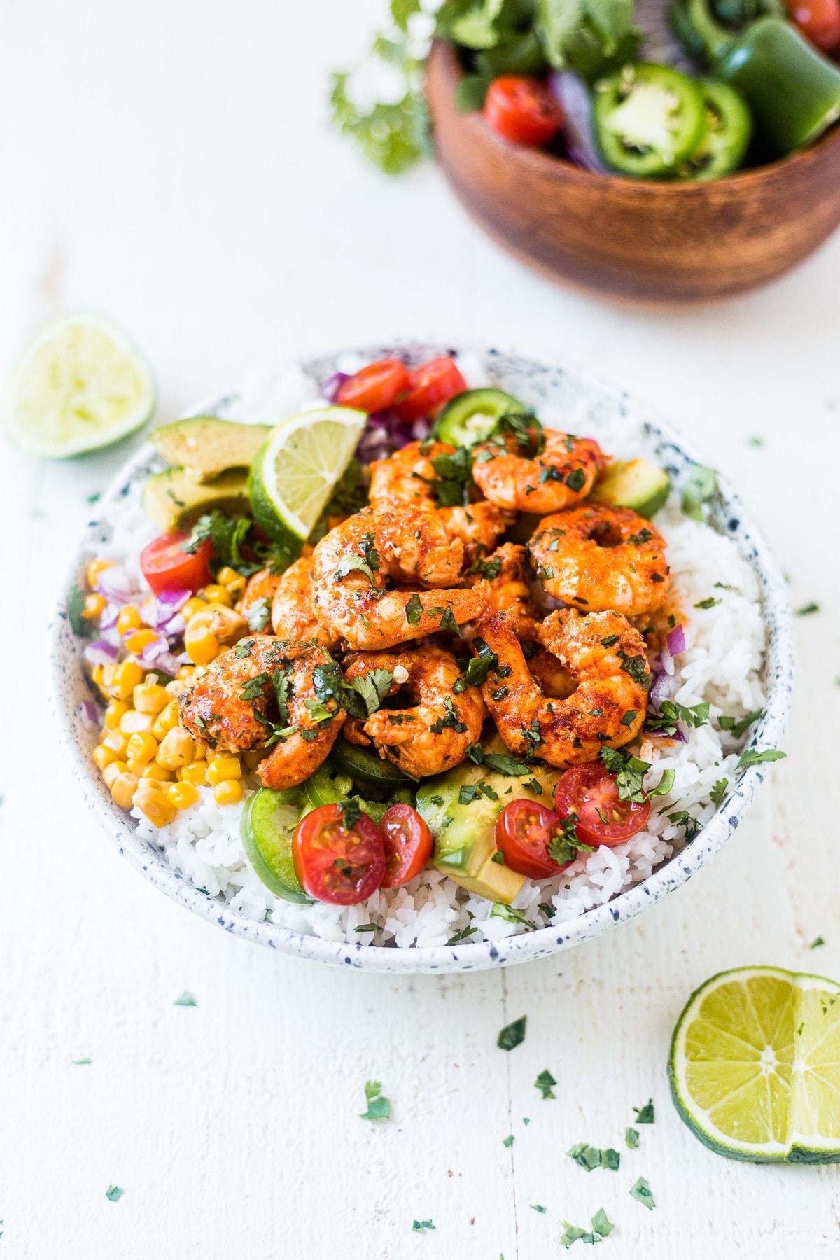 shrimp bowl with white rice and topped with fiesta shrimp, avocado, corn, tomatoes, avocado and fresh cilantro