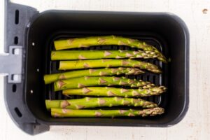 uncooked asparagus in an even layer in the basked of an air fryer