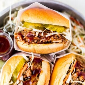 instant pot pulled pork sandwiches in a dish with bbq sauce and pickles