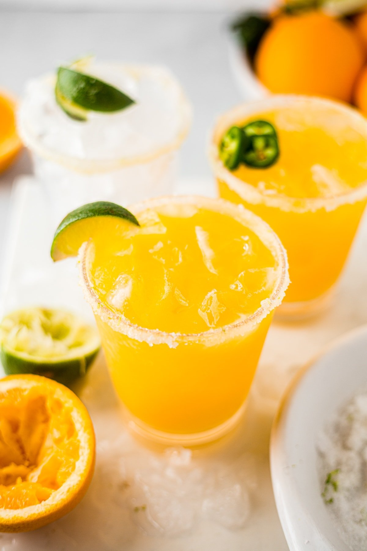 two mango margaritas on the rocks with salt rims and limes and jalapeno as garnish