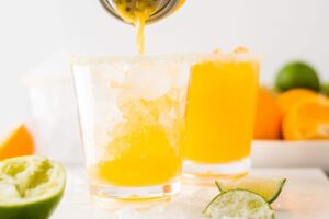 pouring mango margaritas over ice in a small glass cup