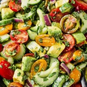 close up of cucumber tomato avocado salad tossed in a cilantro dressing
