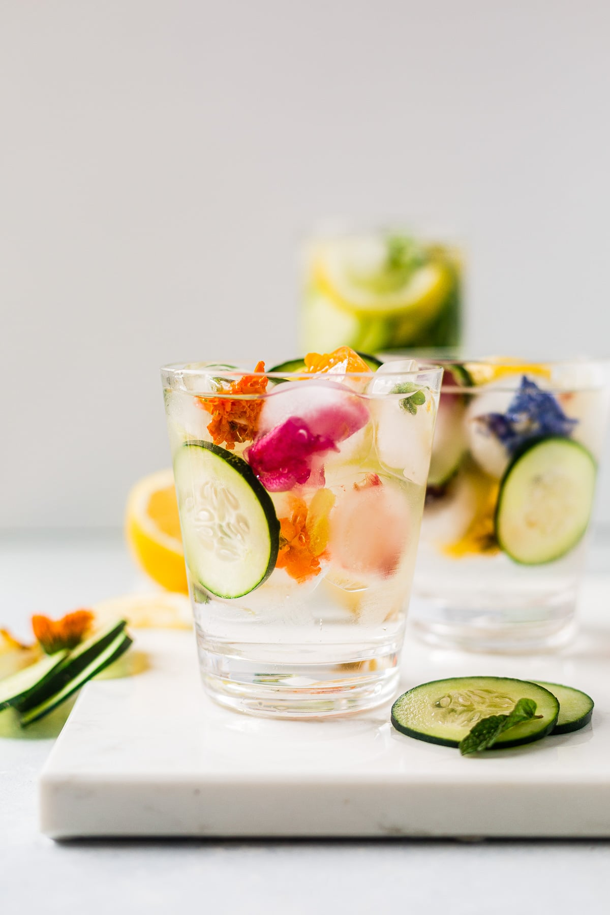 cucumber and lemon water in a cup served with edible flower ice cubes