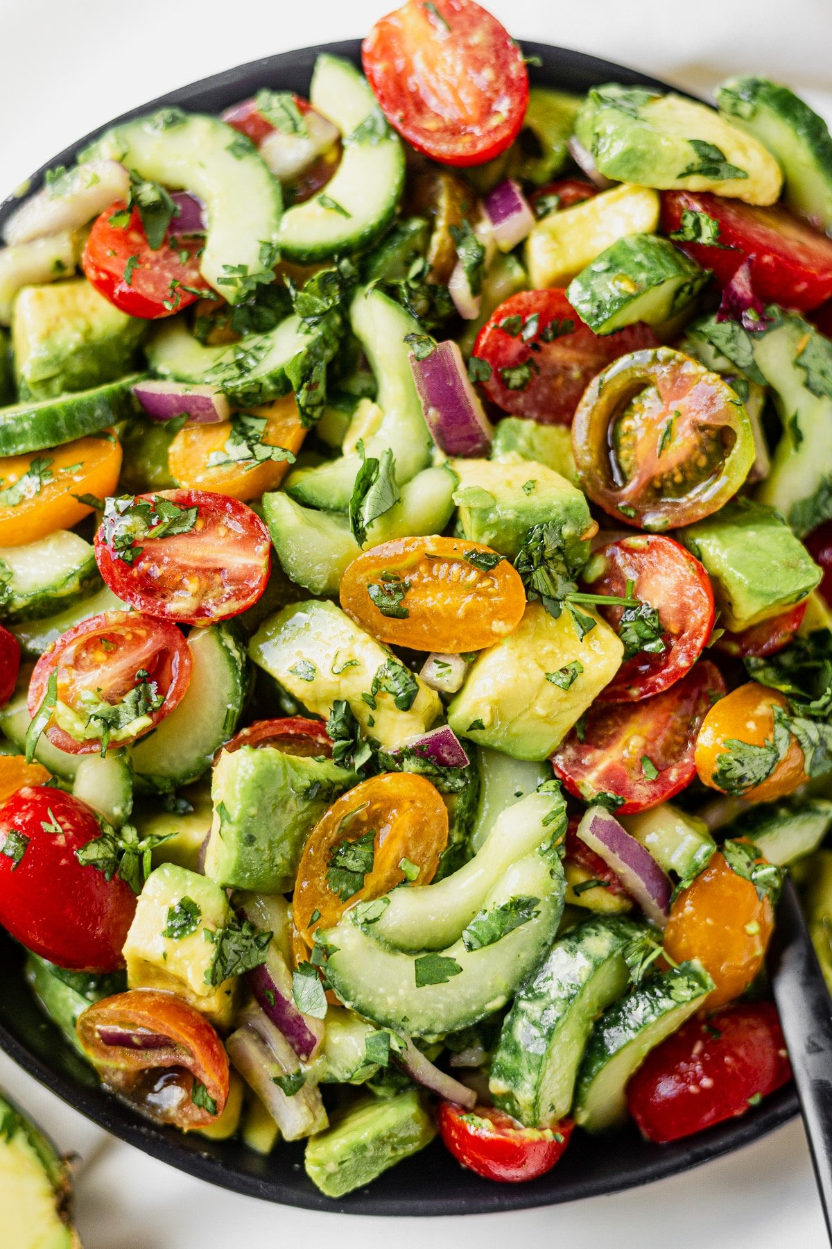 close up shot of cucumber tomato and avocado tossed together in a black salad bowl with a cilantro lime dressing