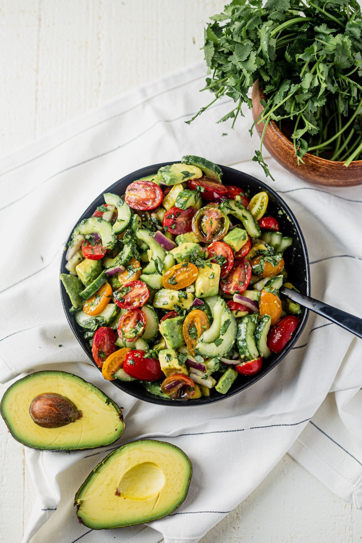 cucumber tomato avocado salad tossed with a cilantro lime dressing in a black serving bowl with fresh avocado on the side
