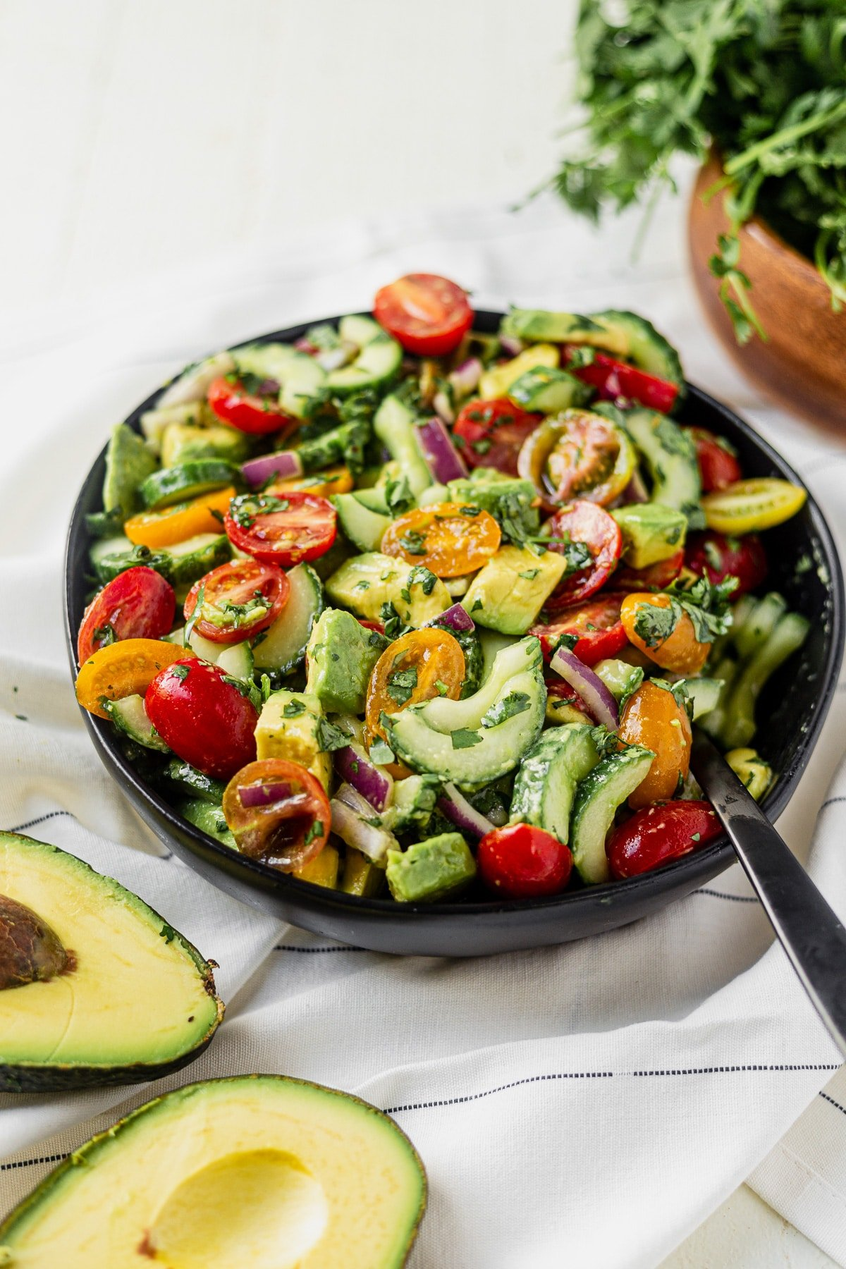 cucumber tomato onion avocado salad in a black serving bowl with a black serving spoon