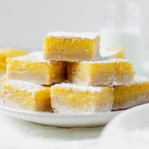 7 gluten free lemon bars stacked on a white plate so you can see the layers of shortbread crust and lemon curd then topped with confectioners' sugar