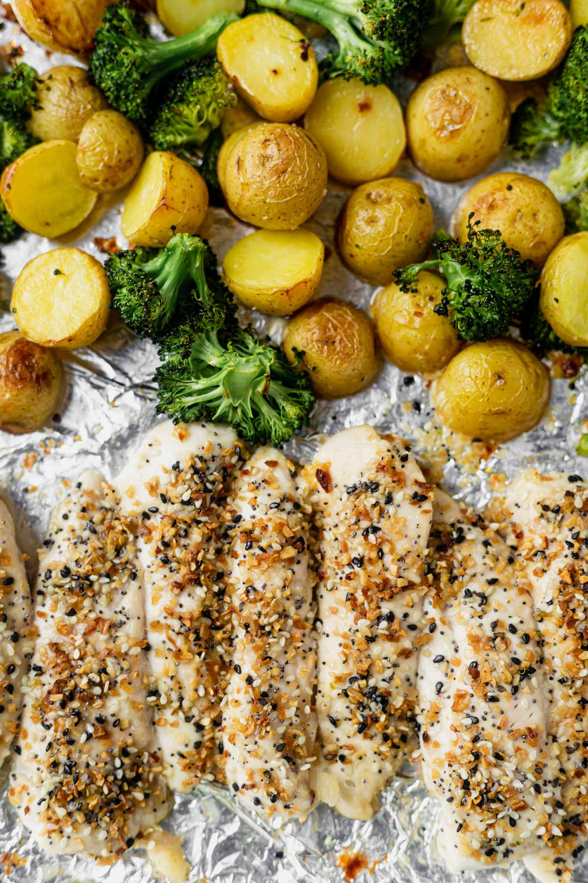 everything bagel chicken tenders on a foil wrapped sheet pan with roasted potatoes and broccoli