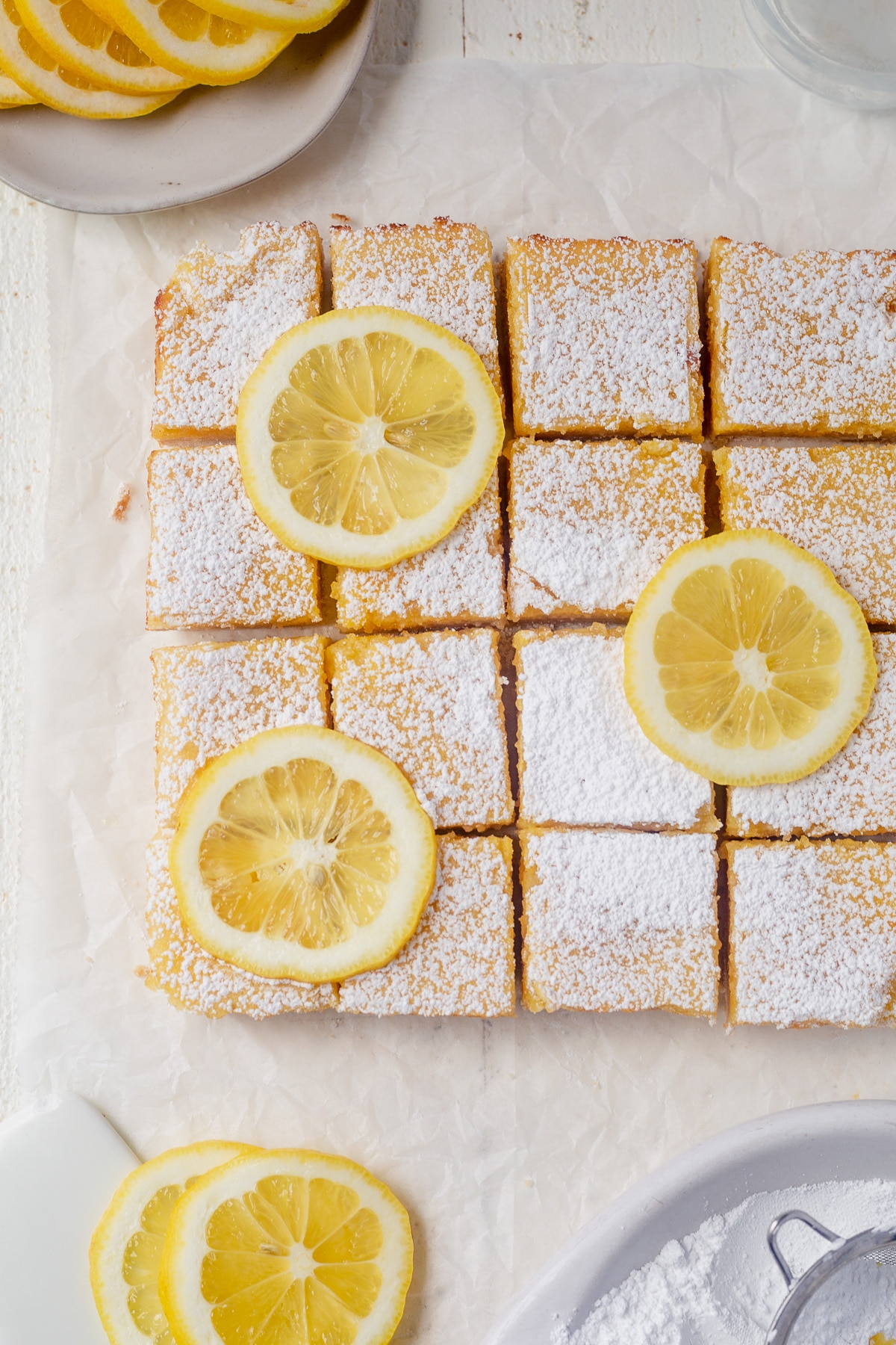 a pan of gluten free lemon bars cut into 12 squares on parchment paper and stopped with confectioners' sugar and lemon slices