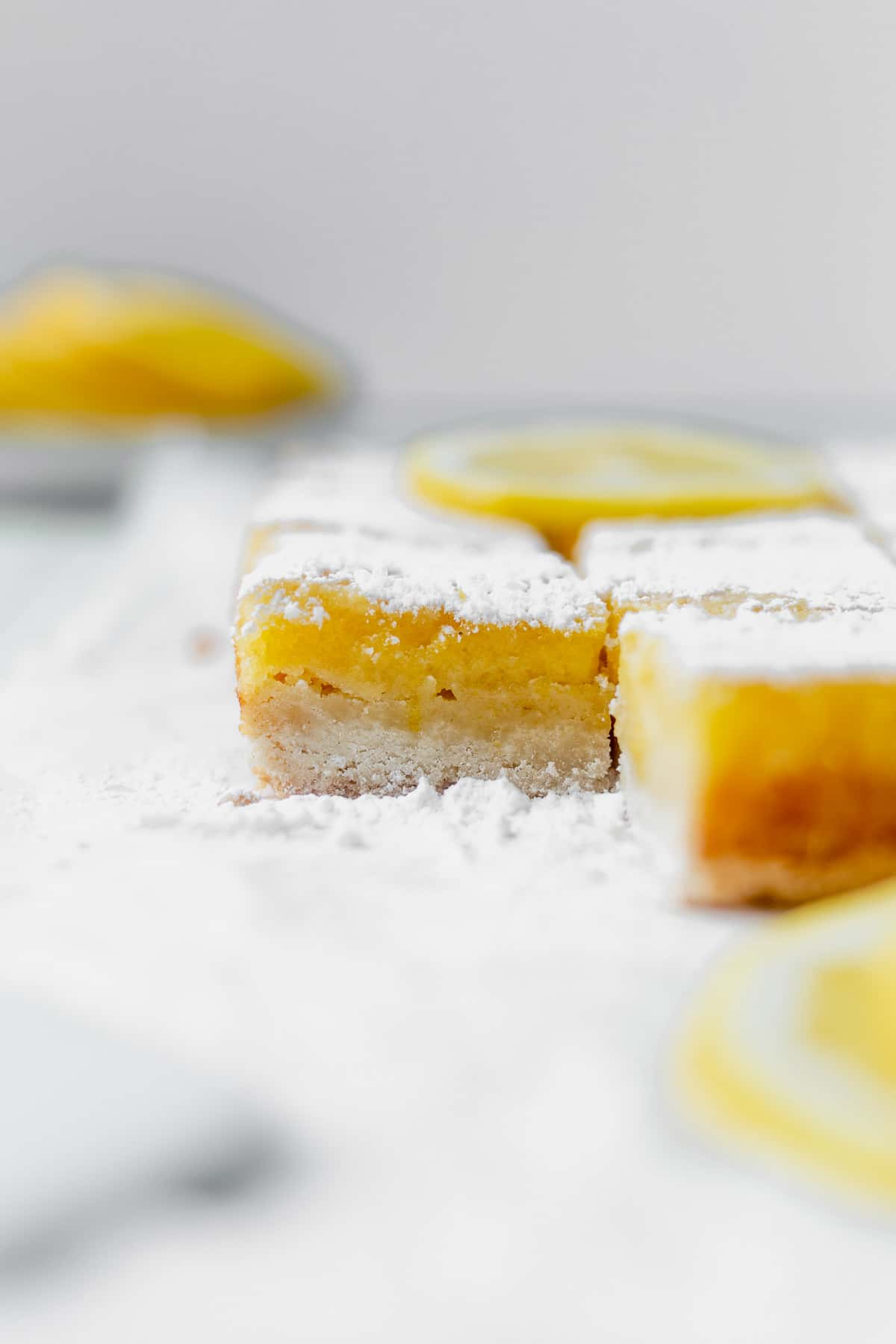 gluten free lemon bars on a piece of parchment paper after they've been cut into squares