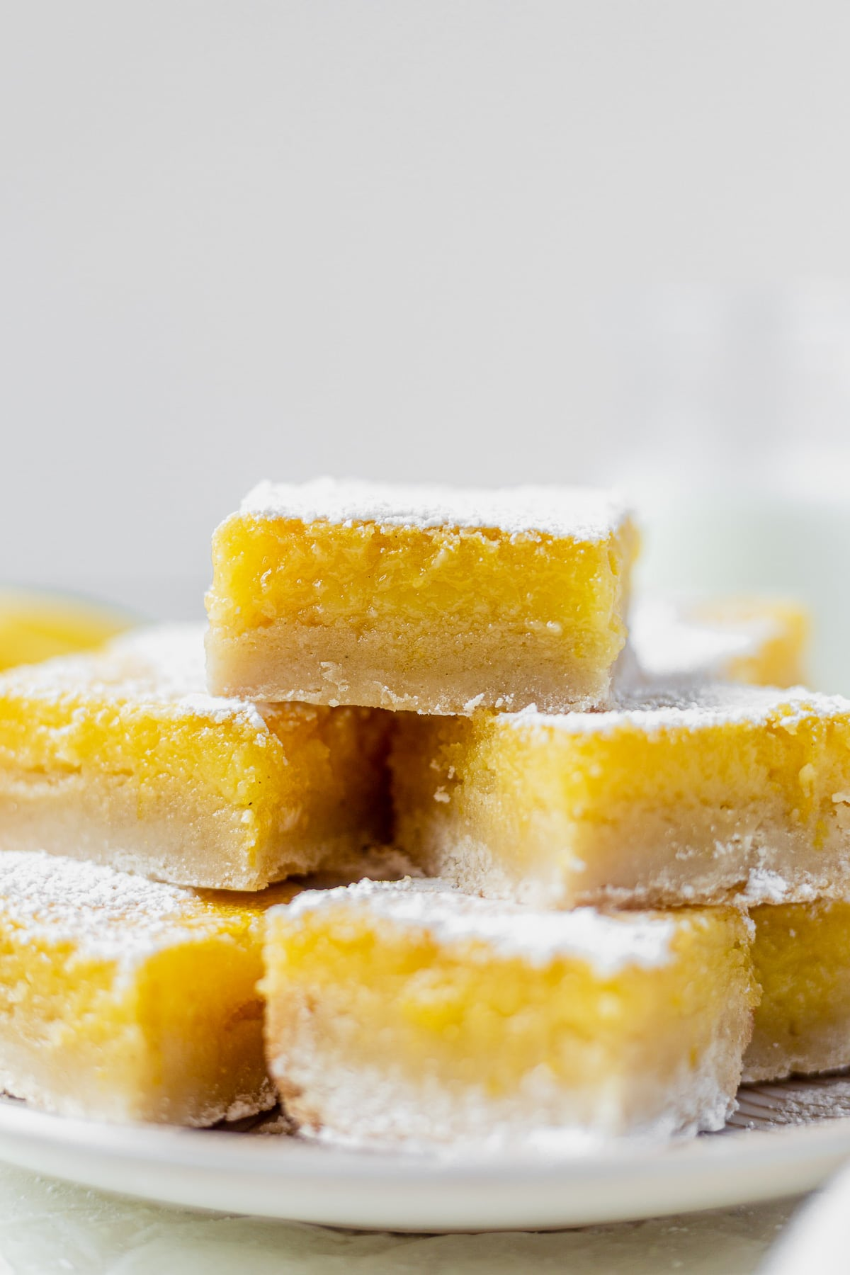 a stack of gluten free lemon bars on a white plate topped with powdered sugar