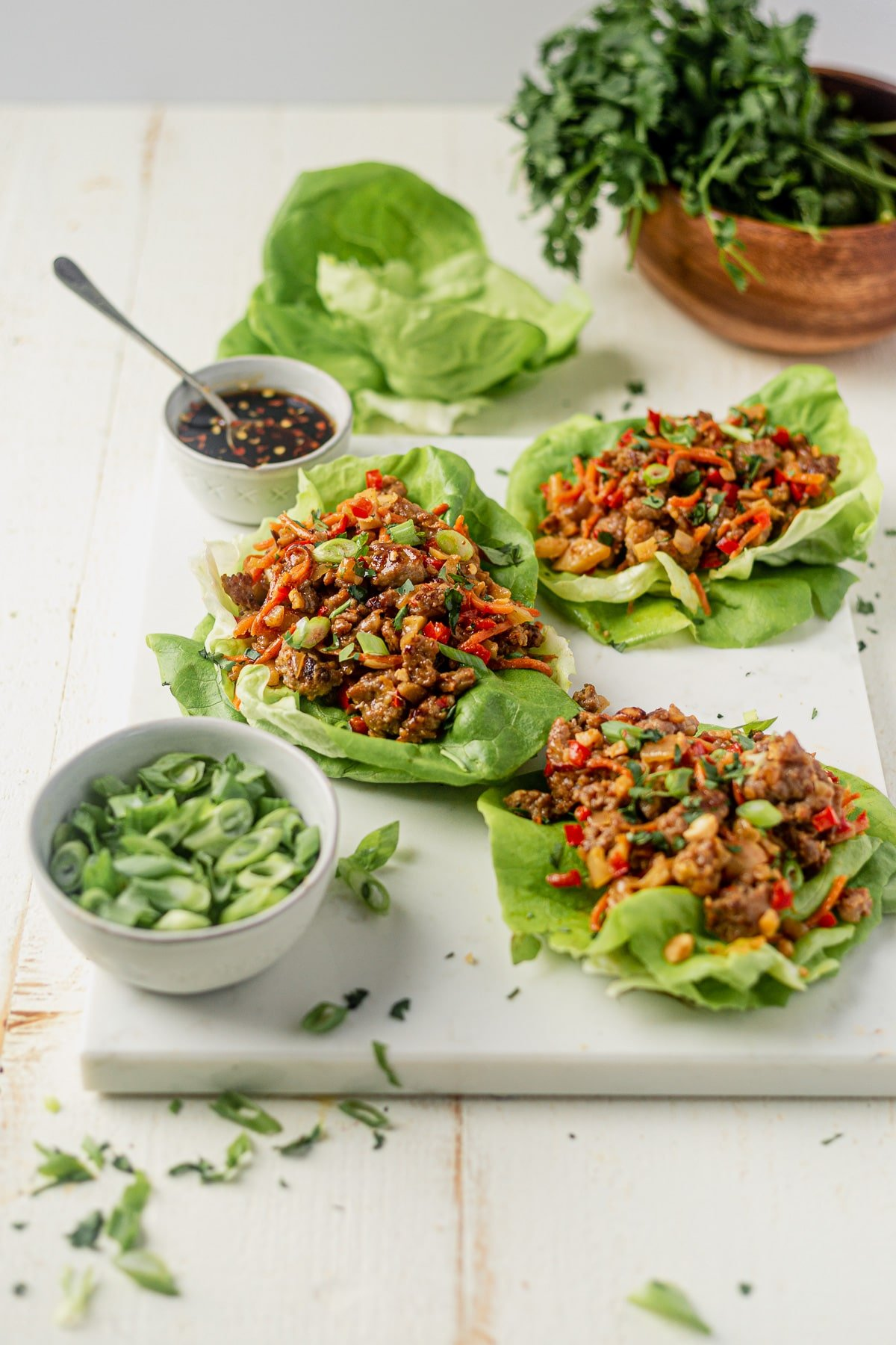 three ground pork lettuce wraps on a white serving tray with sweet and spicy sauce and scallions on the side