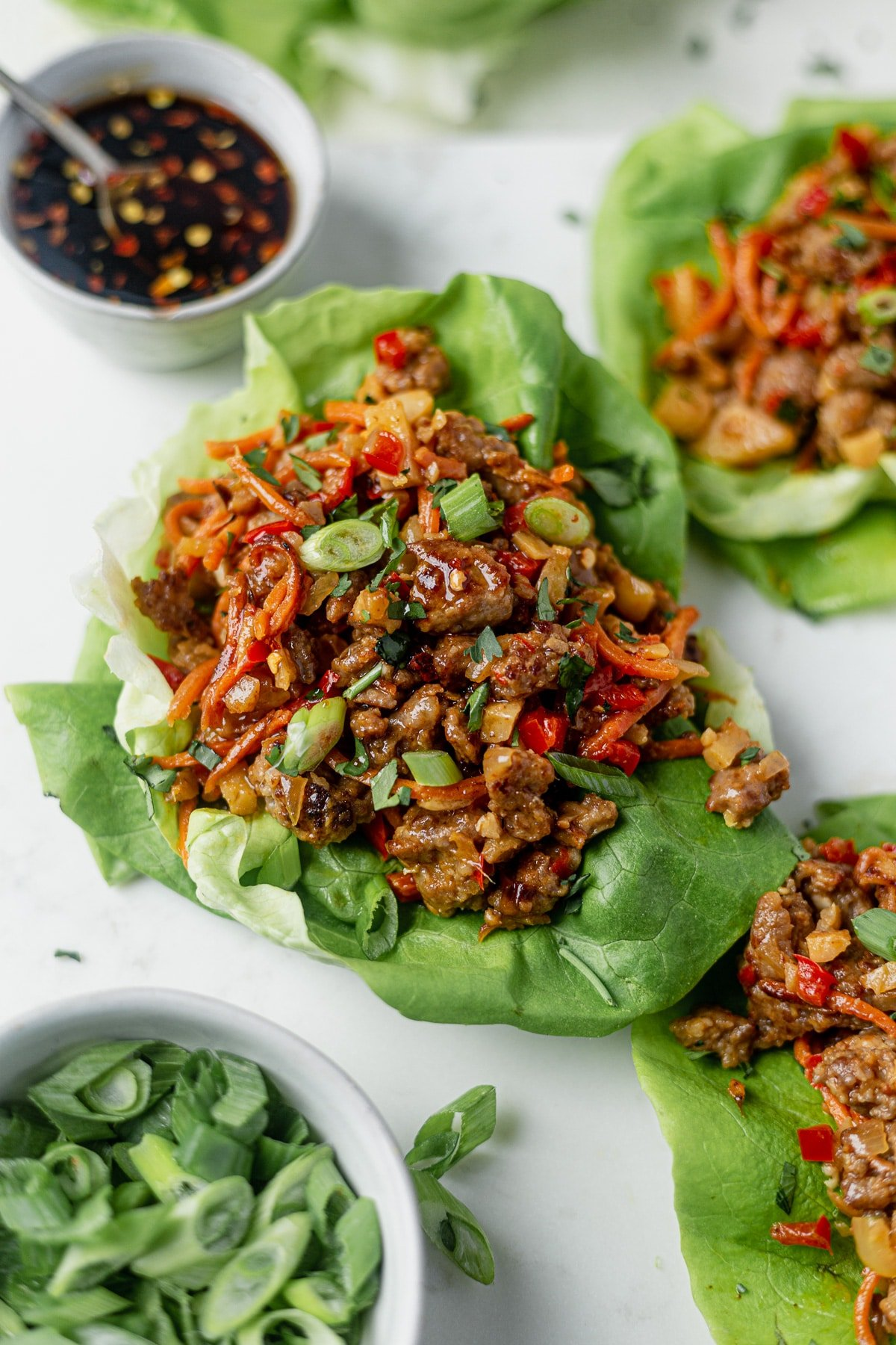 pork lettuce wraps on a white serving tray with spicy sauce and scallions on the side