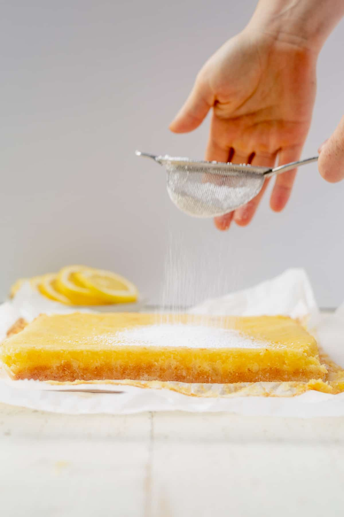 sifting confectioners' sugar over gluten free lemon bars on a piece of parchment paper