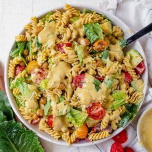 caesar pasta salad in a white serving bowl with a serving spoon