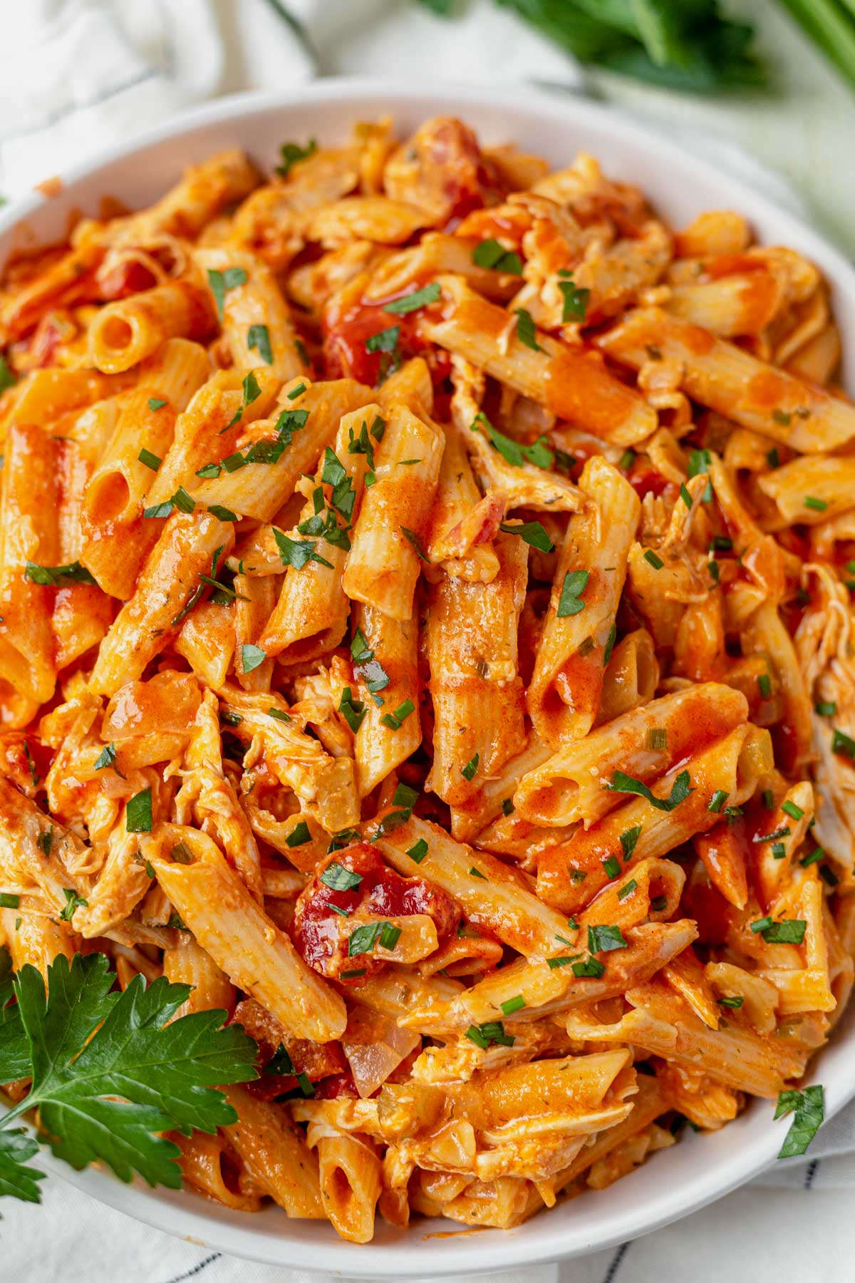 buffalo chicken pasta in a white bowl topped with hot sauce and fresh herbs
