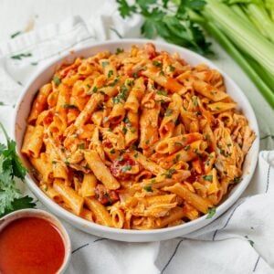 buffalo chicken pasta in a white bowl topped with parsley and surrounded by extra hot sauce and fresh celery