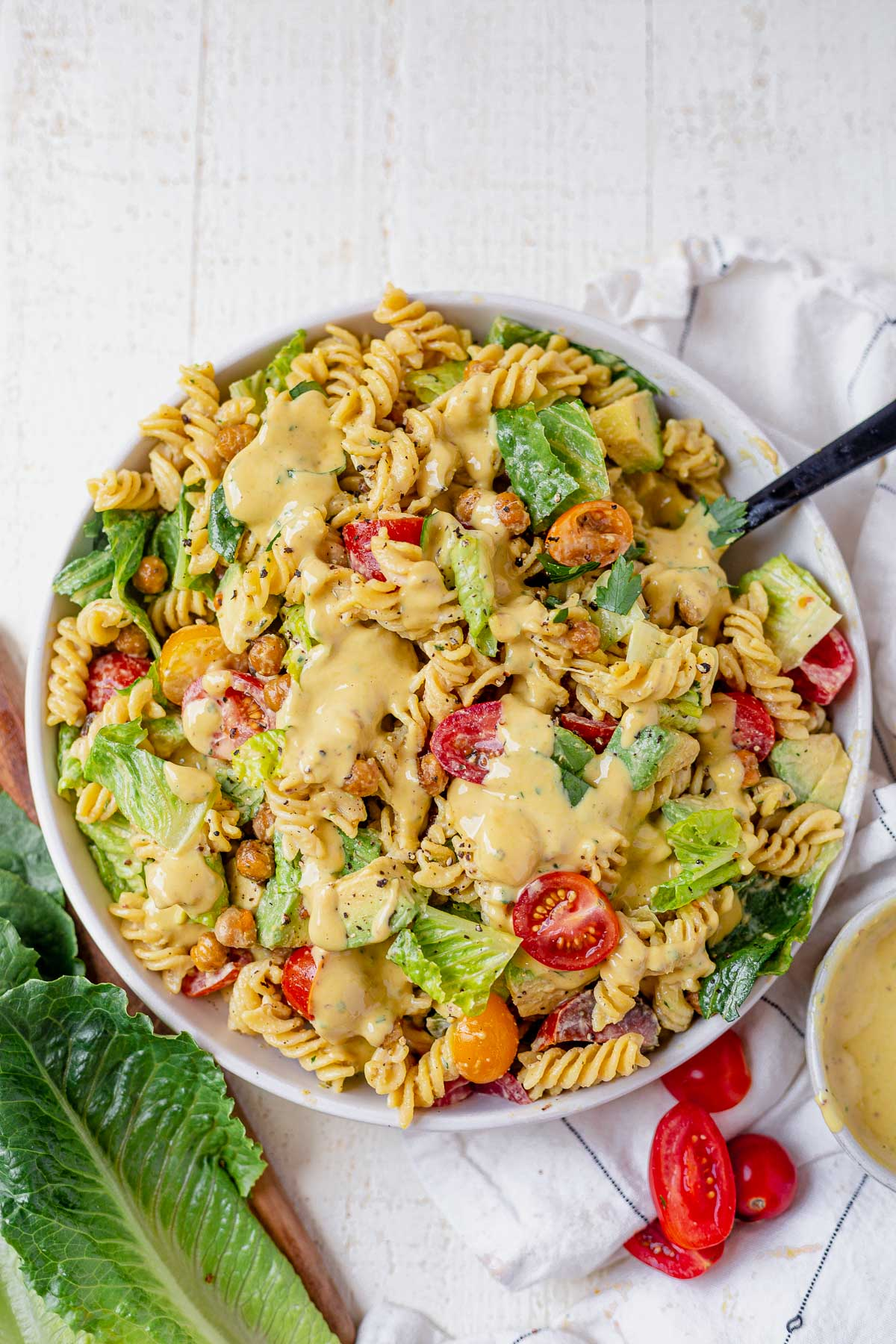 creamy caesar pasta salad in a big white serving bowl topped with more caesar dressing and romaine and tomatoes surrounding it