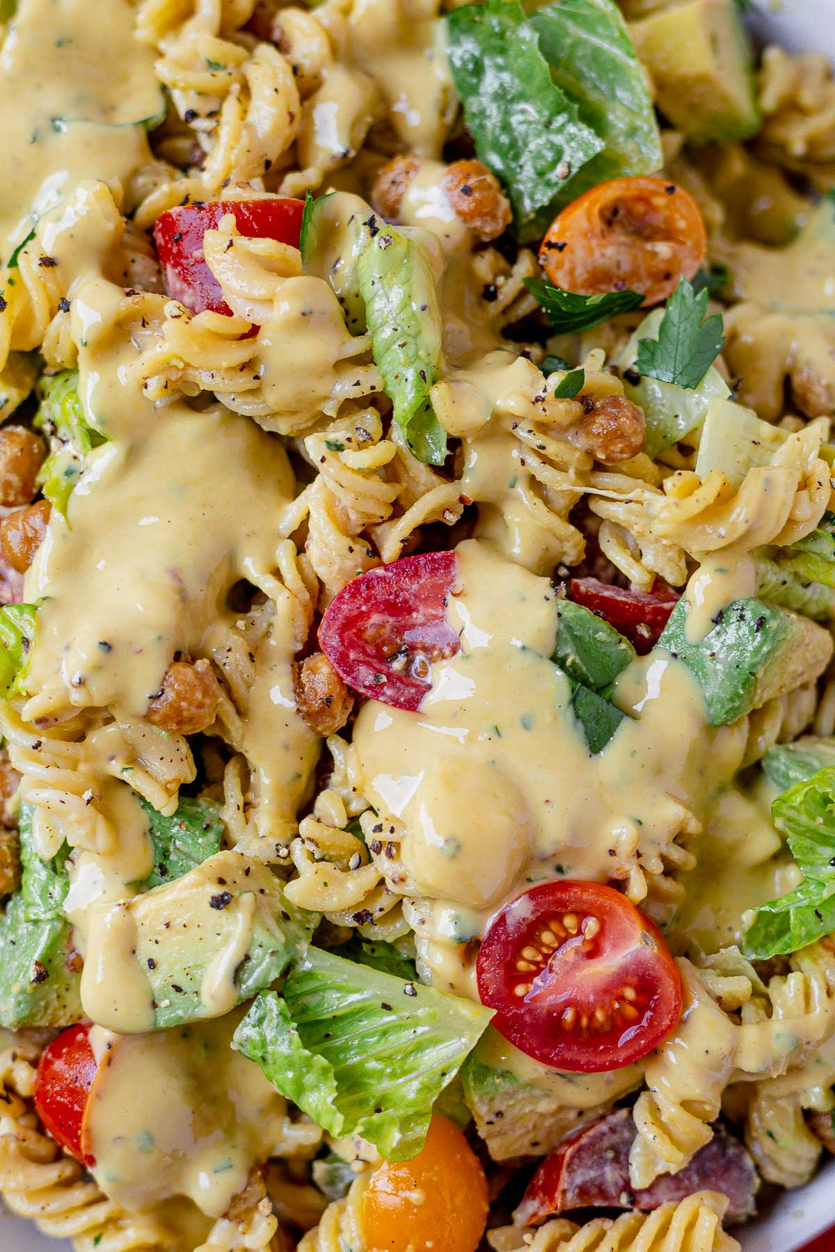 close up shot of caesar pasta salad made with halved cherry tomatoes, chopped romaine, chickpeas and avocado dressing in a creamy caesar dressing