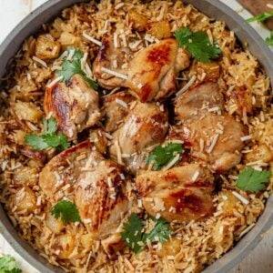 6 hawiian chicken thighs in a skillet with coode basmati rice and topped with toasted coconut and cilantro