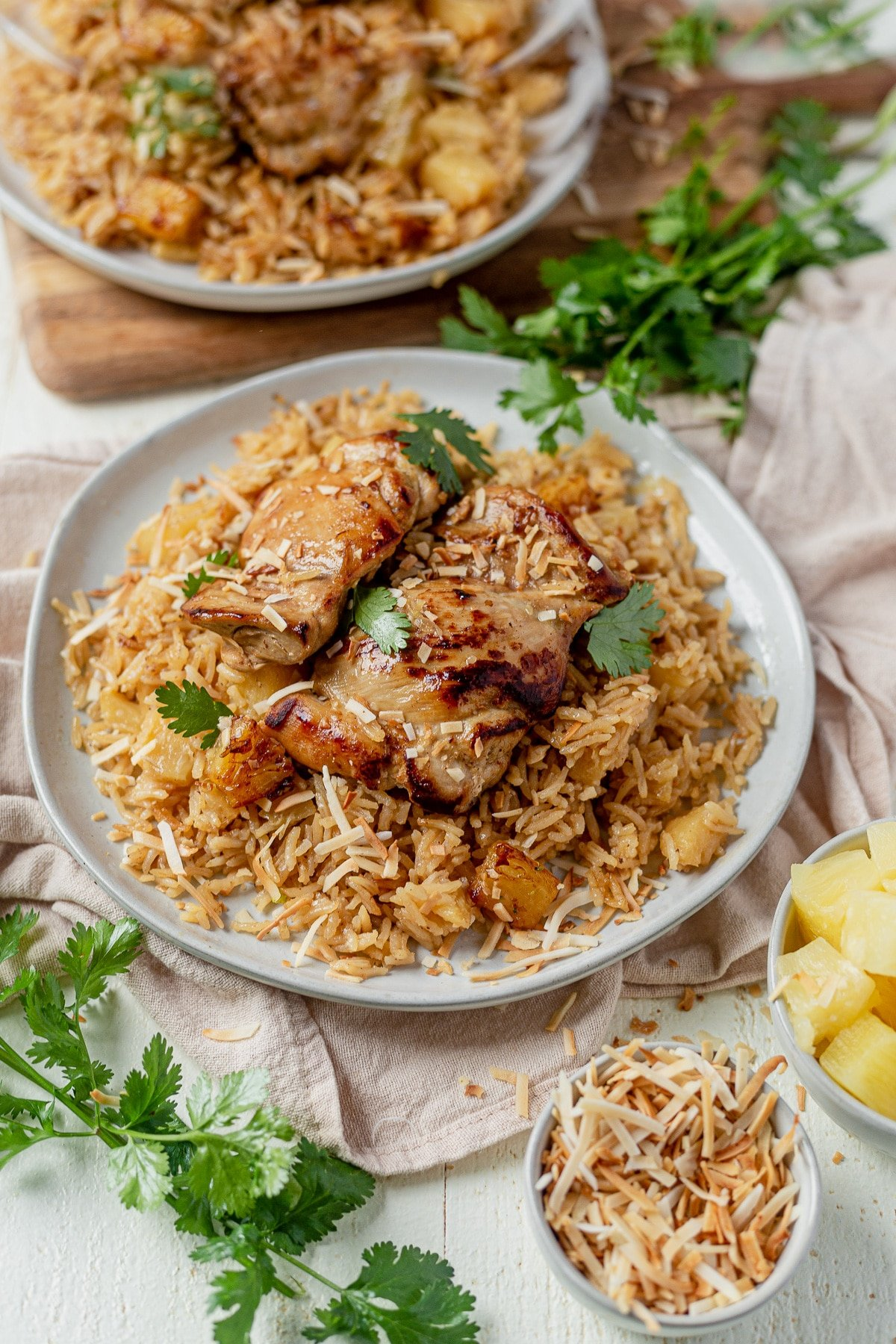 two plates of crispy seared Hawiian chicken on top a bed of coconut rice with coconut flakes and cilantro on top