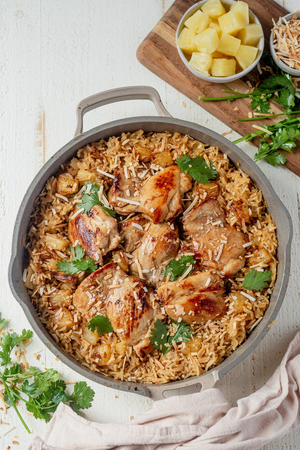Hawaiian chicken thighs on top of a bed of coconut rice and topped with cilantro and shredded coconut all cooked in one pot