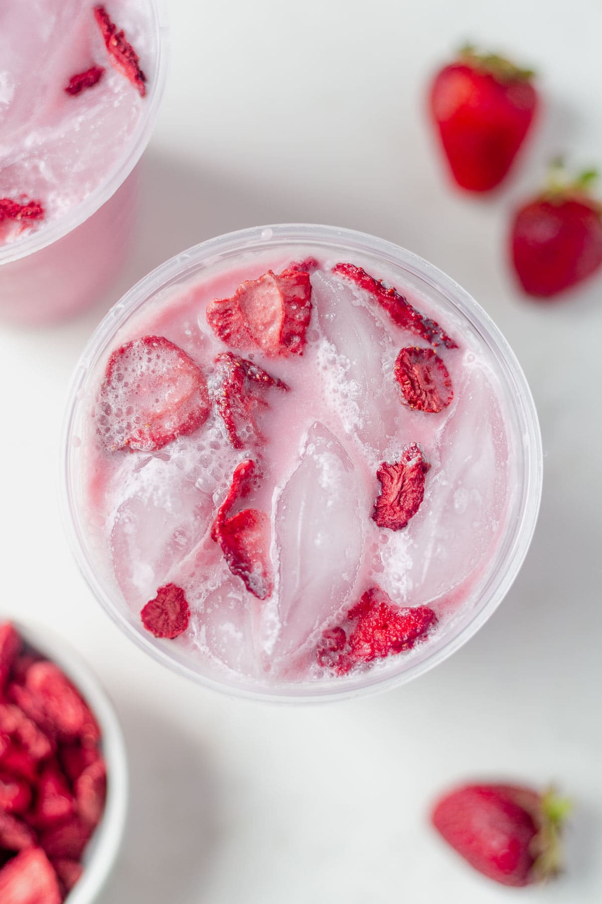 overhead shot of a keto pink drink recipe in a starbucks cup with ice and freeze dried strawberries