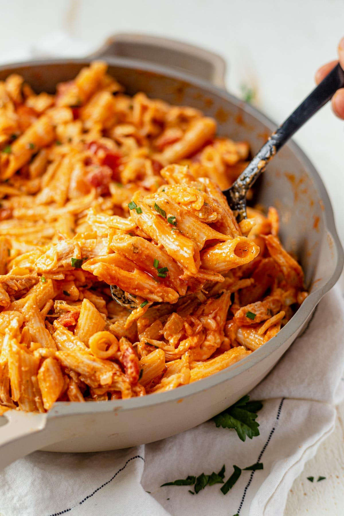 a black spoon scooping out buffalo chicken pasta from a cream colored skillet