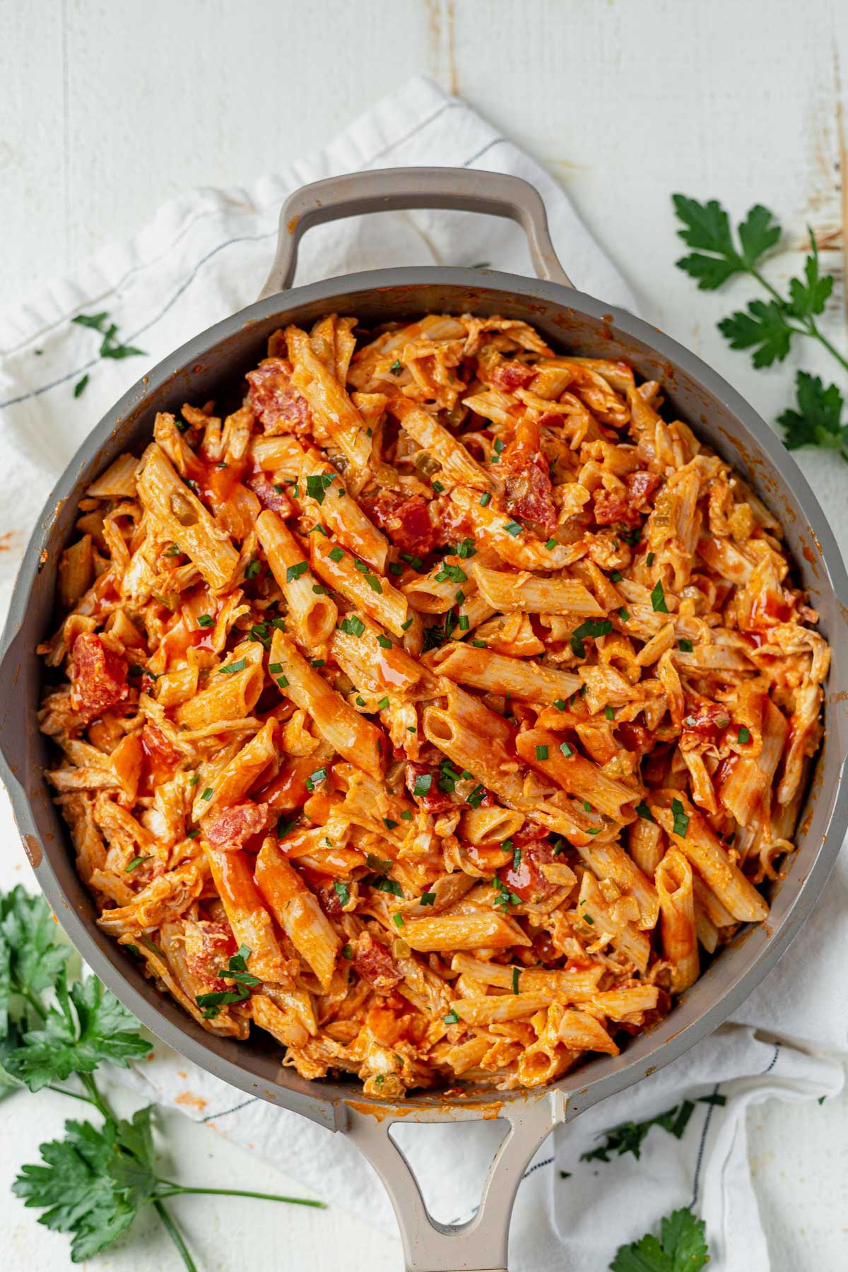 buffalo chicken pasta in a deep skillet topped with chopped parsley