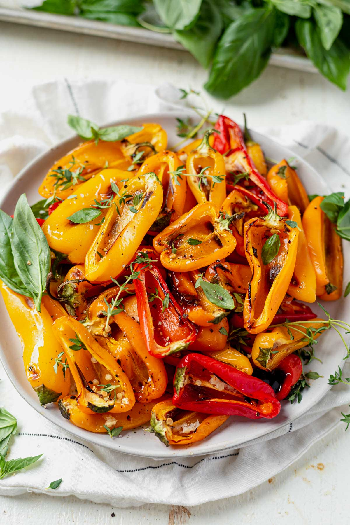 roasted sweet mini peppers cut in half and served on a white dish with fresh basil and thyme