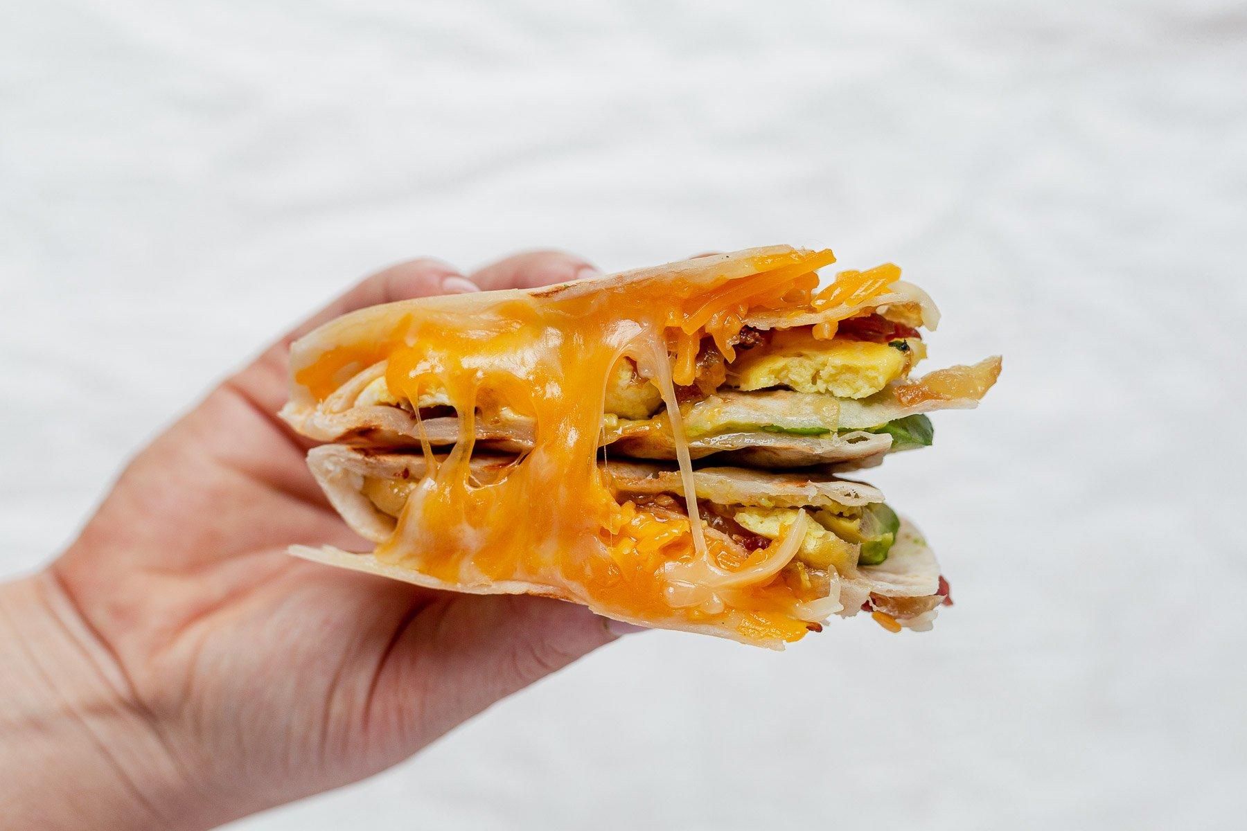 hand holding a cheesy breakfast quesadilla cut in half