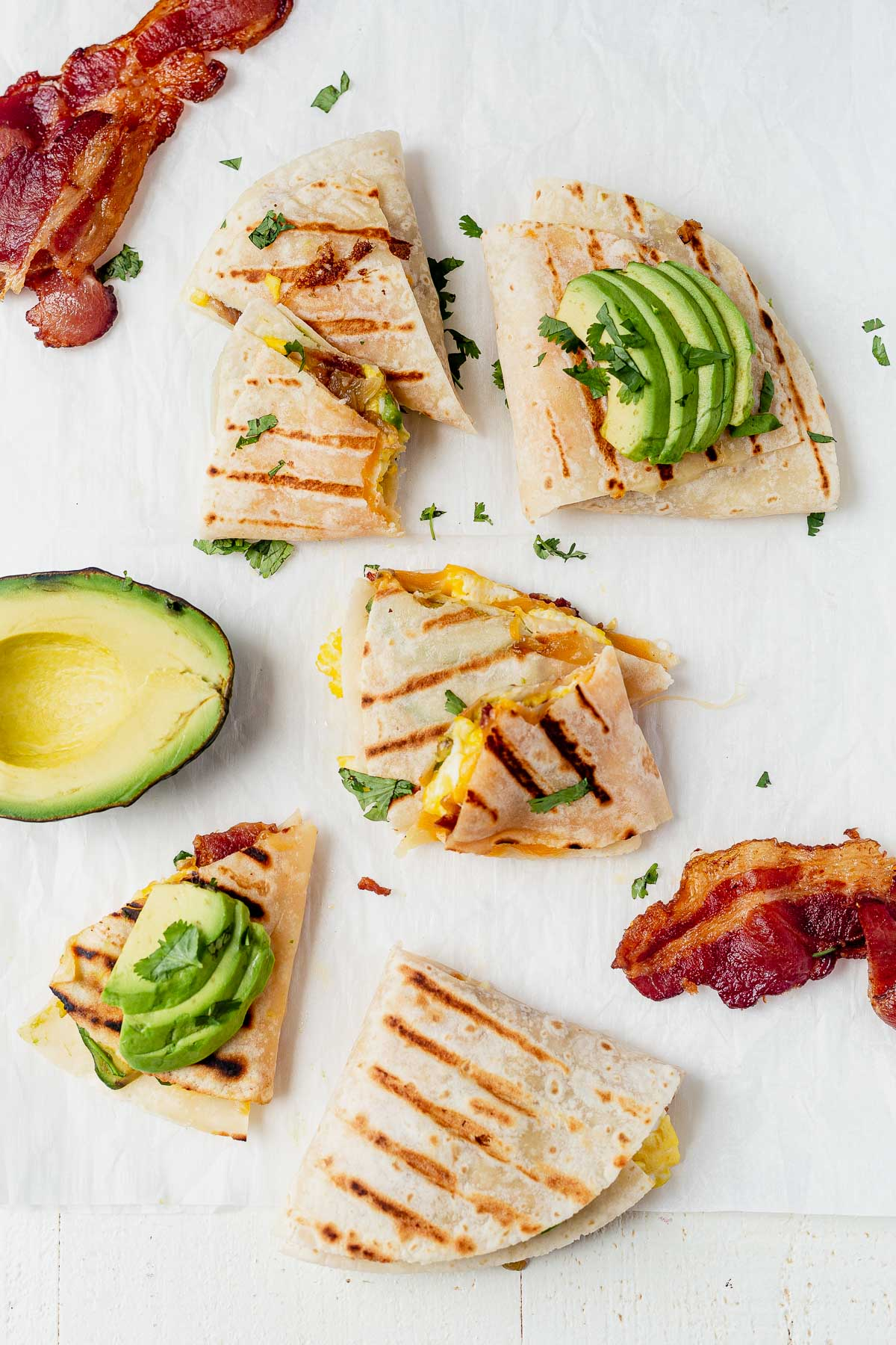 breakfast quesadillas with grill marks on parchment paper with bacon and avocado