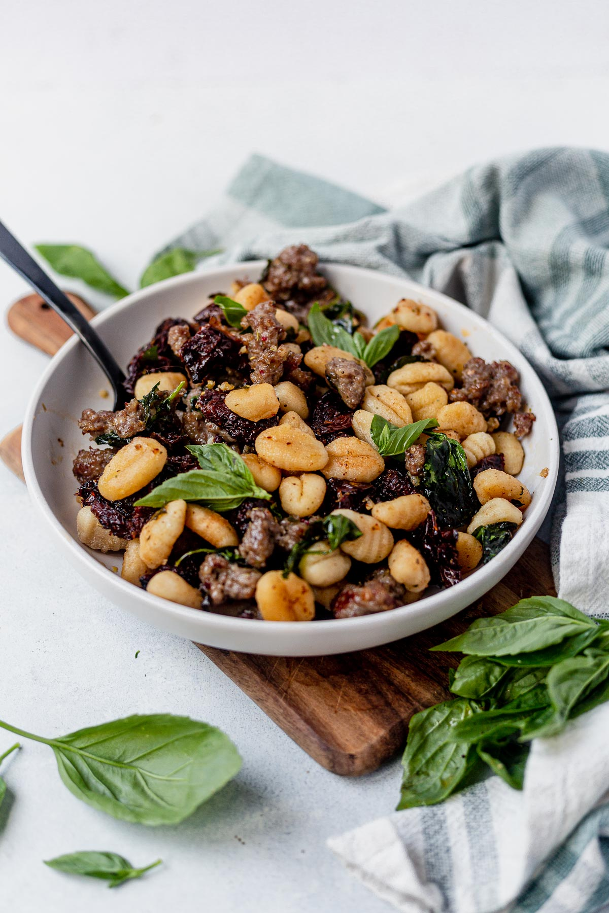 sheet pan gnocchi served in a white bowl topped with basil