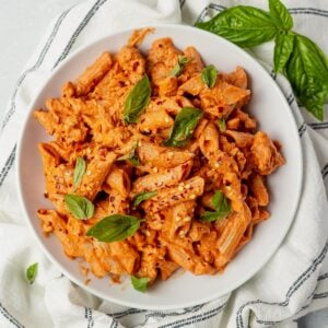 creamy penne arrabbiata in a white bowl topped with basil