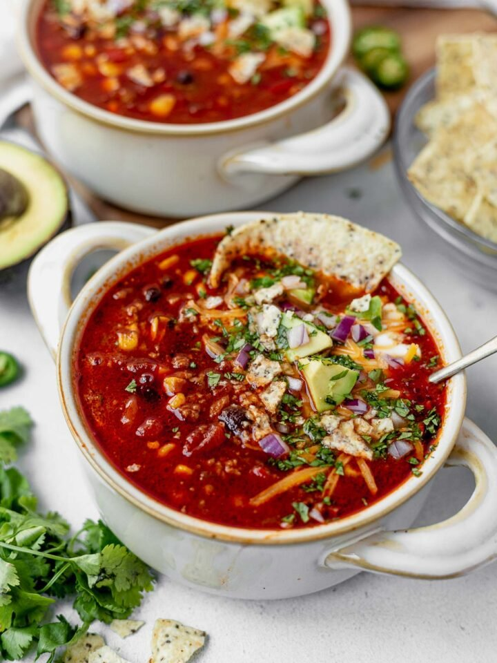 a bowl of instant pot taco soup topped with avocado, cheese, cilantro and sour cream