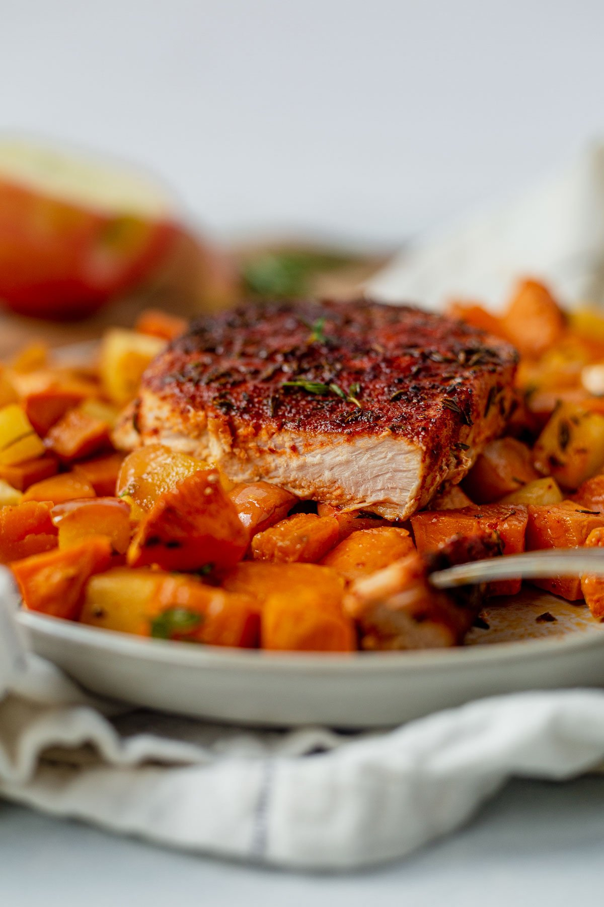 a piece of pork chop with a bite taken out sitting on top of a bed of sweet potatoes and apples