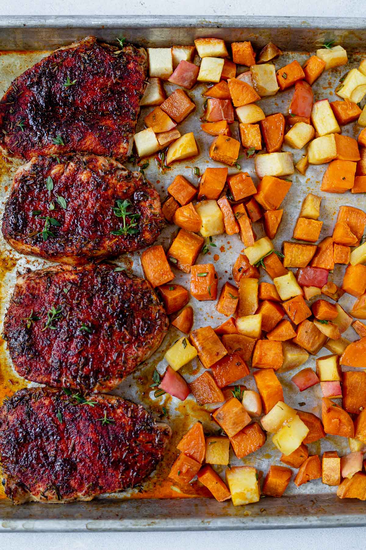 seasoned pork chops on a sheet pan with roasted sweet potatoes and apples
