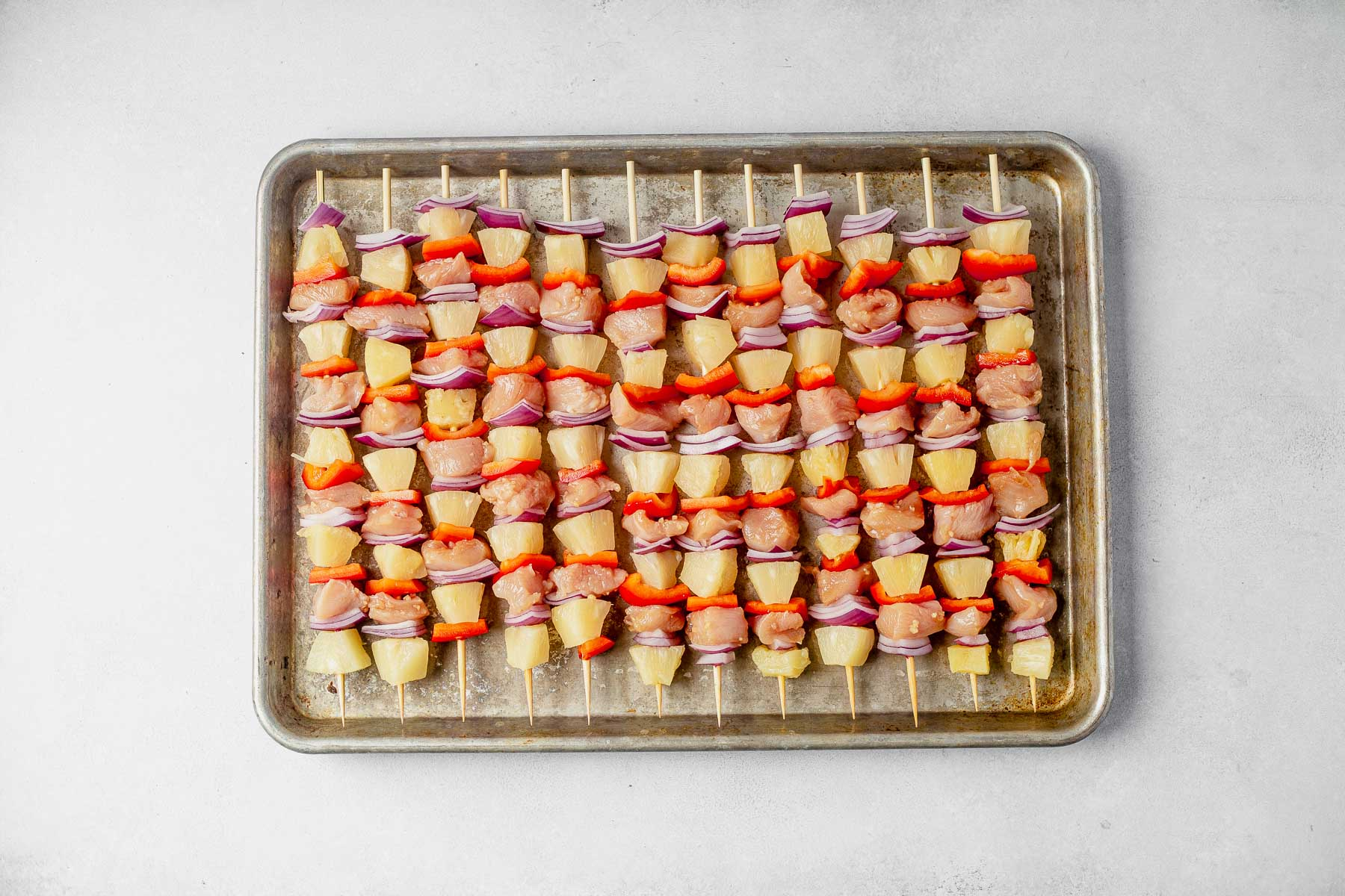 uncooked hawaiian chicken kabobs lined up on a sheet pan before cooking