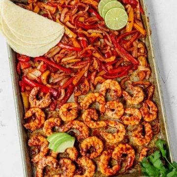 sheet pan shrimp fajitas on a white table with tortillas and avocado