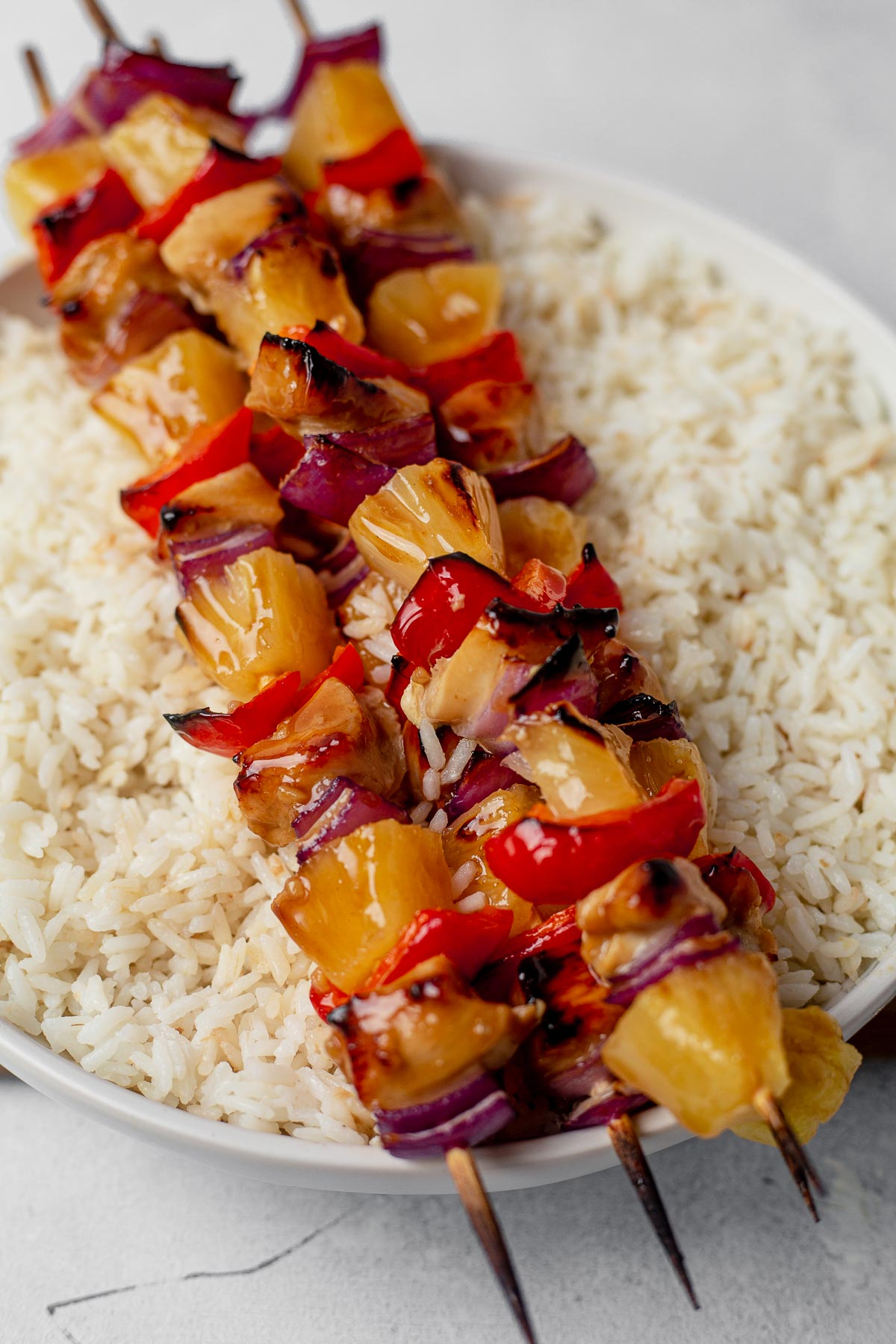 three hawaiian chicken kabobs sitting on top of a bowl of coconut rice