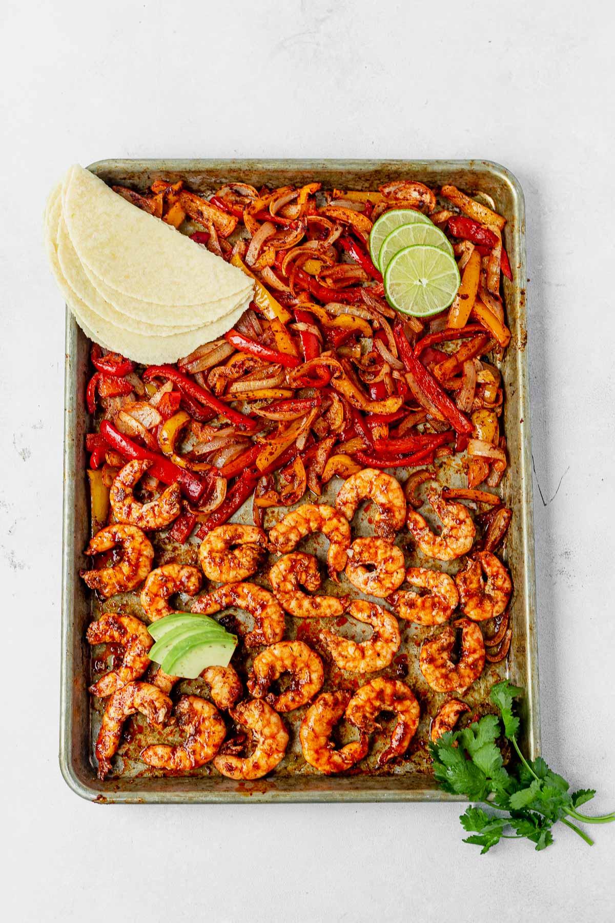 sheet pan shrimp fajitas with taco shells, avocado and cilantro on the side
