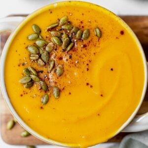 creamy panera autumn squash soup recipe swirled in a bowl and topped with pumpkin seeds