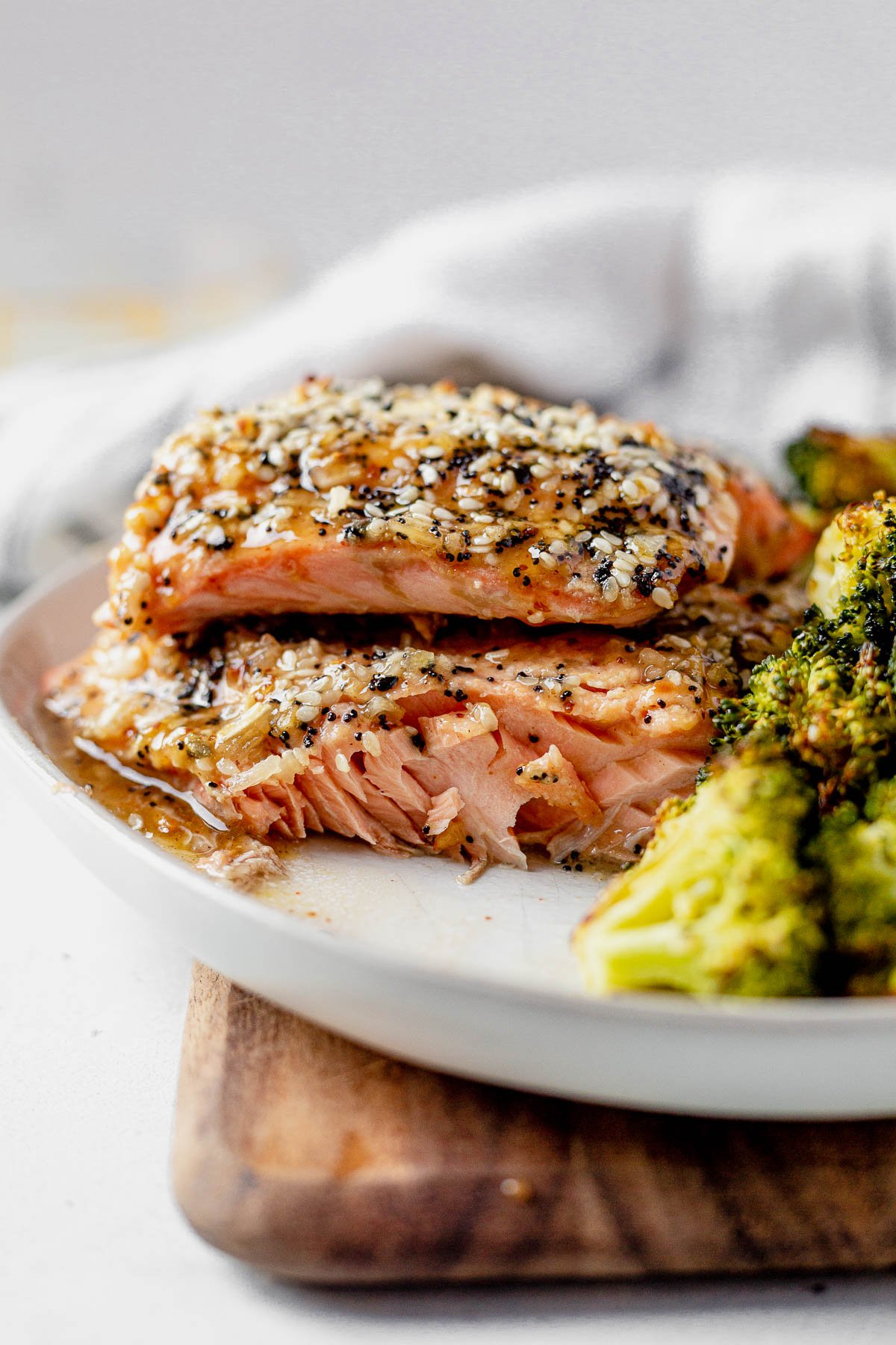 everything bagel seasoning salmon fillets on a white plate with the flaky center showing