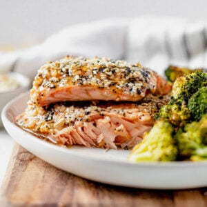 flaky salmon fillet on a white plate with everything bagel seasoning and a side of roasted broccoli