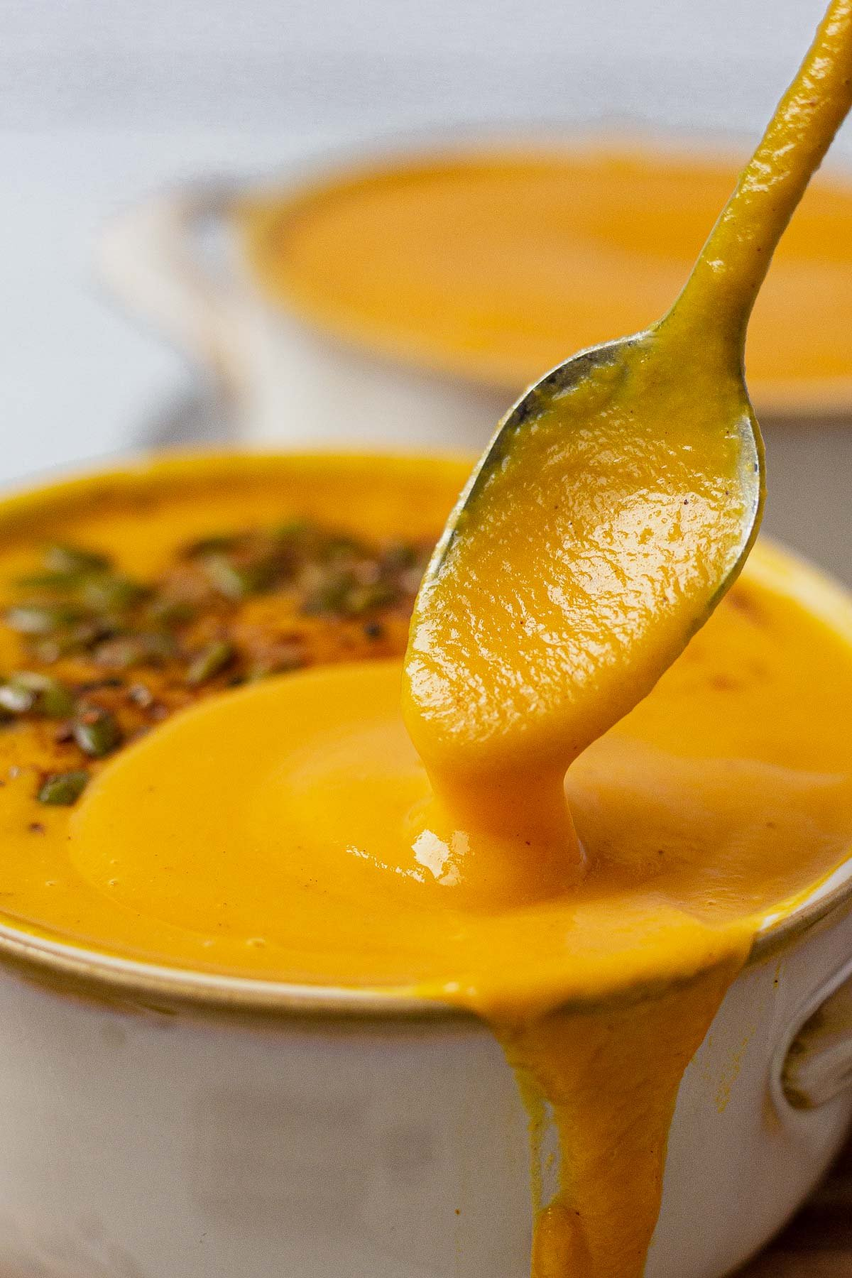 a spoon scooping out homemade creamy panera autumn squash soup from a bowl