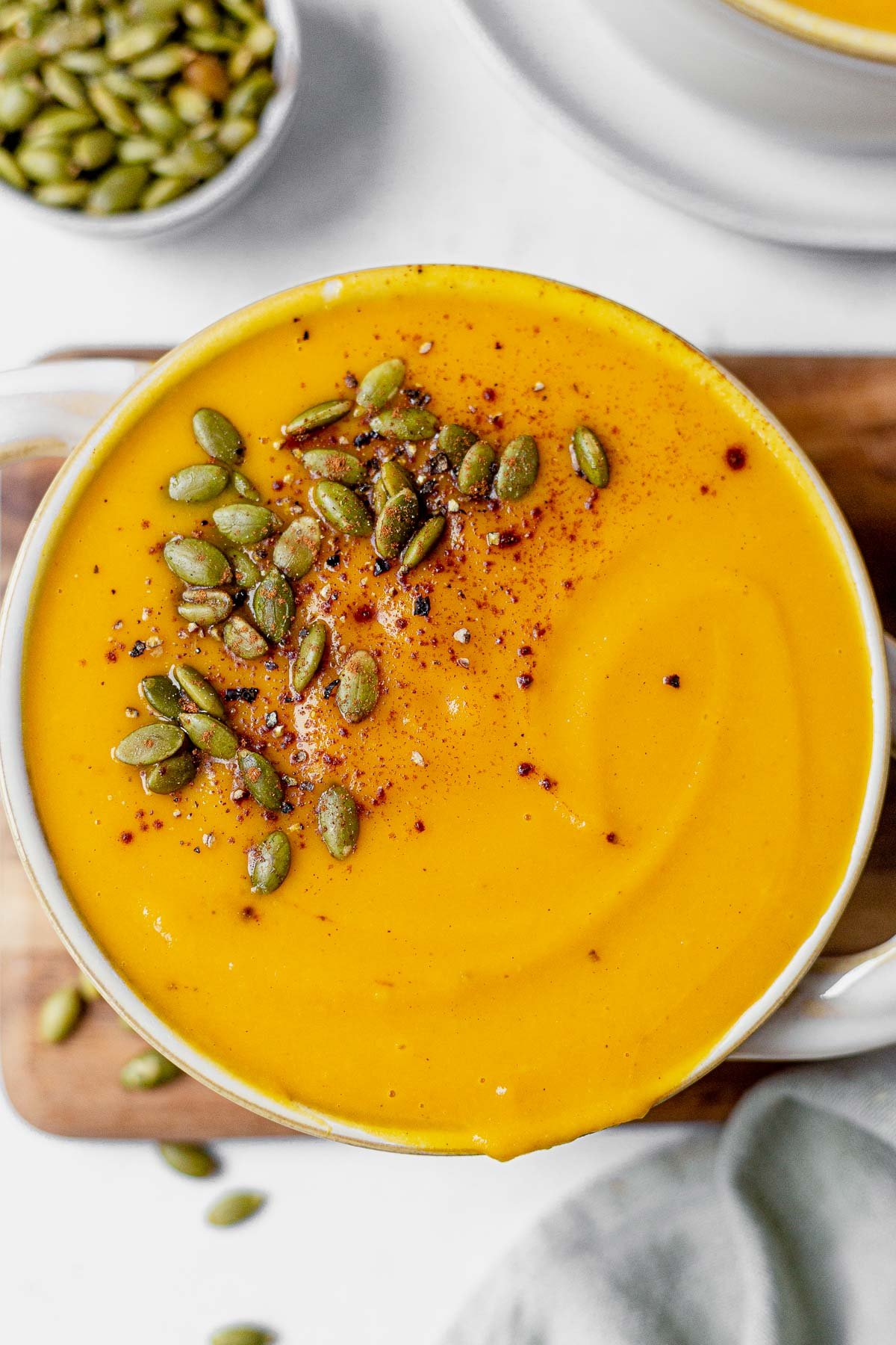 panera bread autumn squash soup recipe in a bowl topped with pumpkin seeds